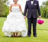 woman in wedding dress and man in tux. holding hands.
